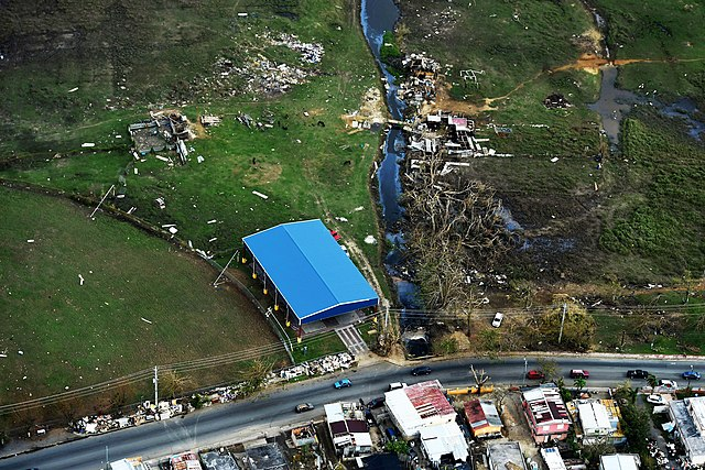 A blue shelter is the only remaining undamaged structure in a field in Puerto Rico where surrounding homes have been destroyed.