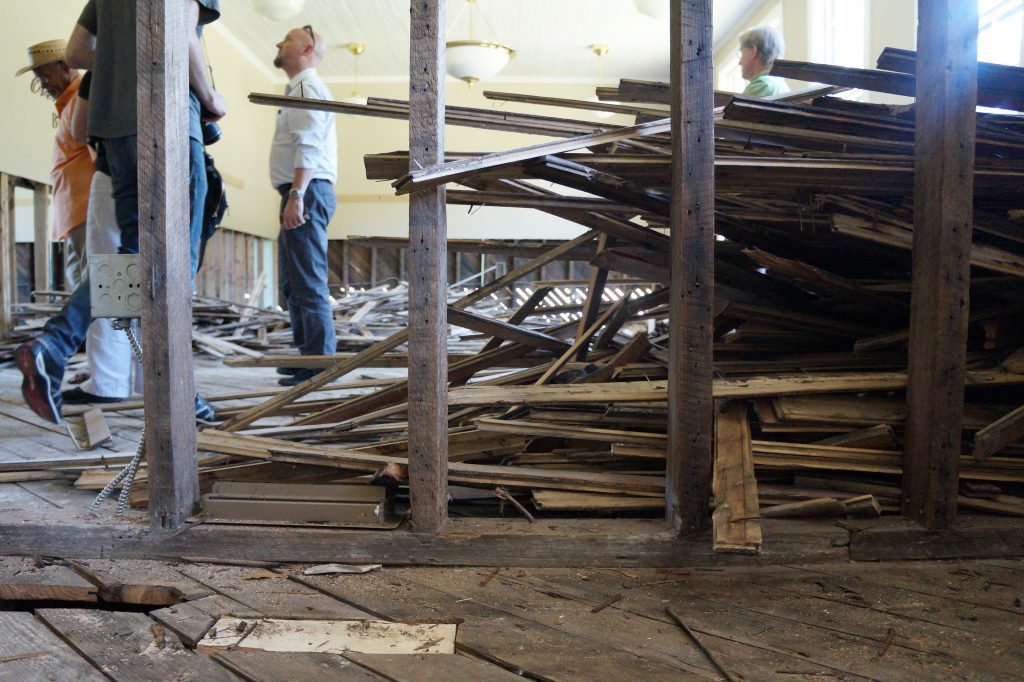Three men stand among piles of wood and debris inside the Princeville town museum following Hurricane Matthew.