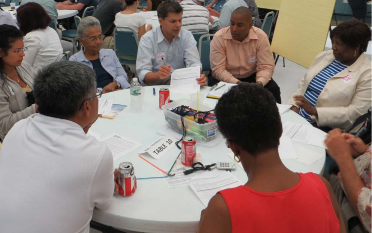 People from diverse backgrounds sit around a table at a public workshop talking