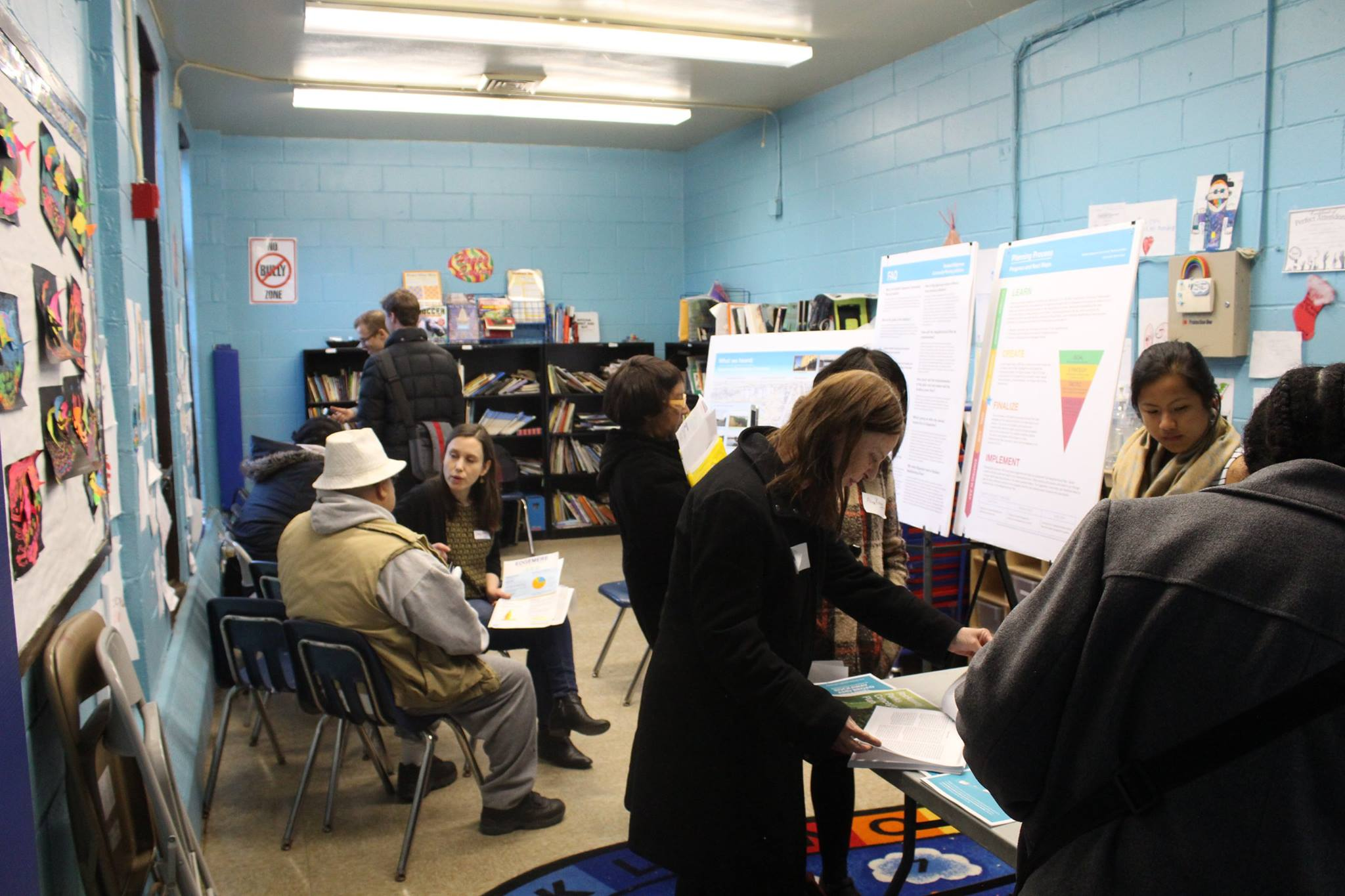 A woman leads a small discussion group of adults in a classroom, talking about resiliency strategies in Edgemere, NY