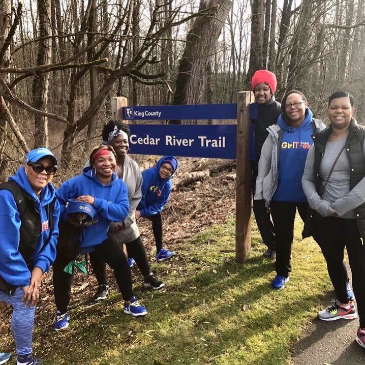 "A group of women and girls stand on a trail in the woods, smiling at the camera. They are wearing athletic pants and sweatshirts, ready for a day of hiking. There is a sign that says ""King County: Cedar River Trail."""