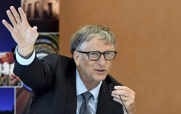 Bill Gates sits at a table and speaks into a microphone, his right hand extended upwards as he speaks