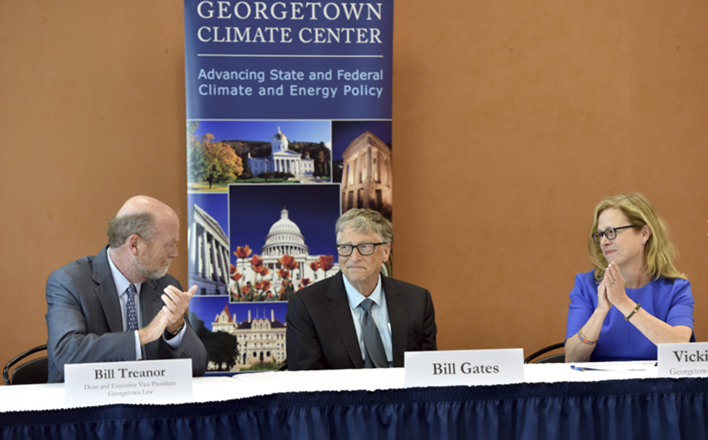 "Georgetown Law Dean Bill Treanor, Bill Gates, and Georgetown Climate Center Executive Director Vicki Arroyo sit side by side at a table in front of a banner that says, ""Georgetown Climate Center: A resource for state and federal policy"" and shows pictures of several State Capitols"