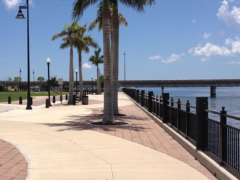 A harbor walk in Punta Gorda, Florida. The brick walkway is dotted with palm trees and streetlights, and the water is visible below.
