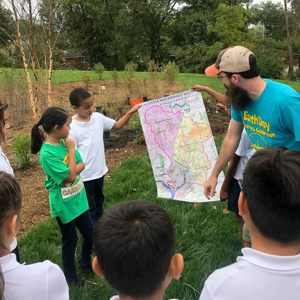 School-age children and an adult educator stand outside near a rain garden and hold up a paper map of the Anacostia Watershed, which they are discussing.