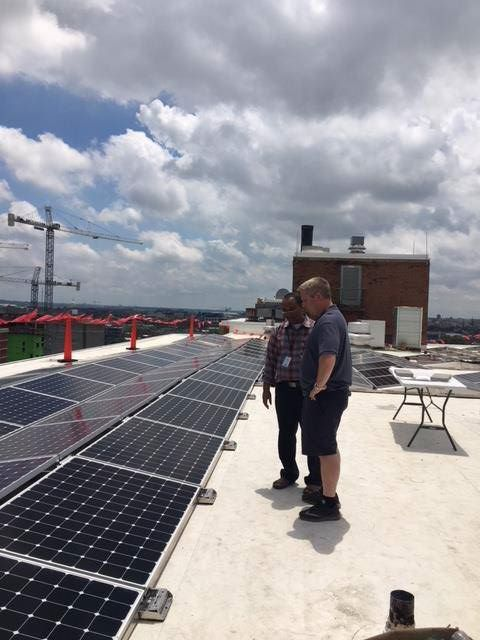 Two men stand on a rooftop by a recently installed solar energy array.
