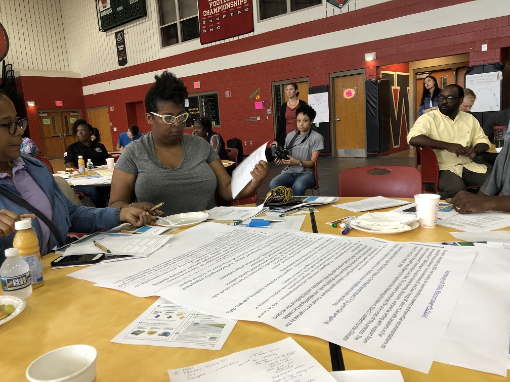 "Two women sit at a table as a public listening session in a school gymnasium. They are reviewing a large poster paper titled ""Summary of EAG Recommendations"""