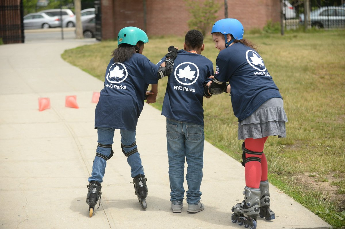 "Three children wearing navy blue shirts with white writing that say ""NYC Parks"" with their backs to the camera. There are two girls on rollerblades and helmets on either side of a boy wearing sneakers."