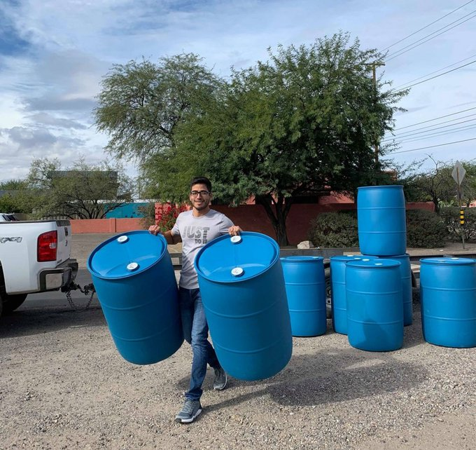 A man carries two empty, large, blue water barrels with stacks of the same type of barrels behind him.