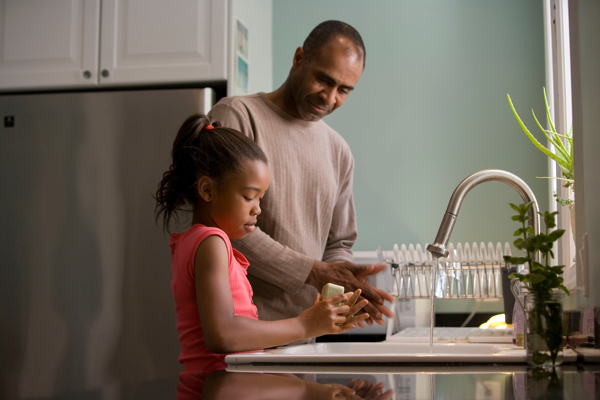 A father and daughter wash their hands in a kitchen sink.