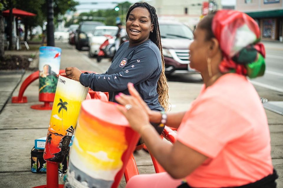 Two women joyfully play colorful drums as part of an art installation in Little Haiti, Miami.