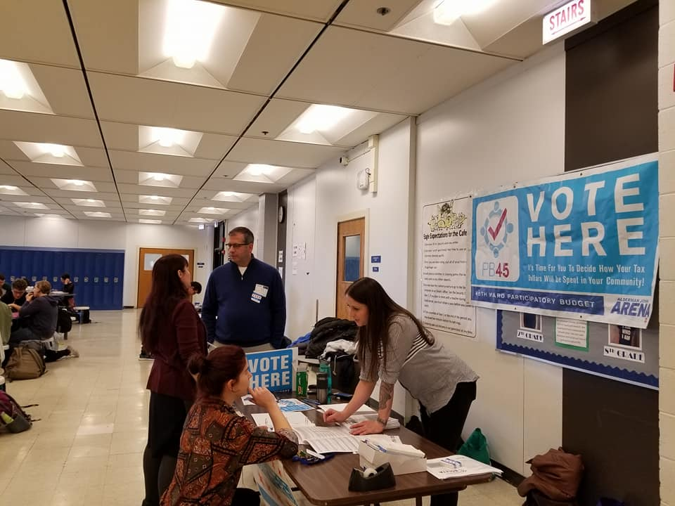 "A woman signs up for participatory voting in Chicago. She kneels on the floor in front of a table, leaning on the table to fill out a form, while another woman on the other side of the table helps instruct her. A blue banner with white text hangs on the wall and reads, ""Vote Here. It's time for you to decide how your tax dollars will be spent in your community!"""