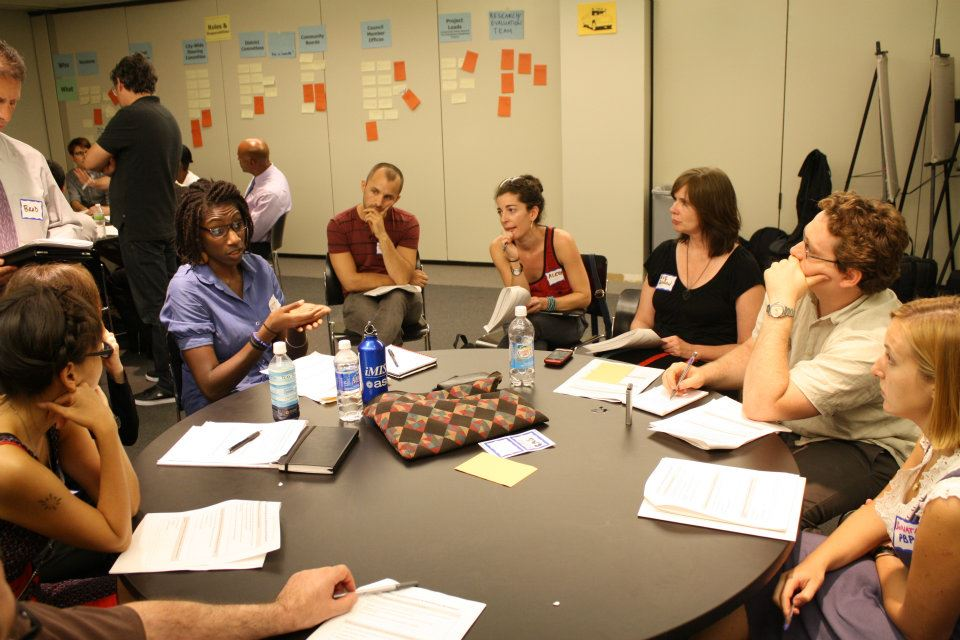 People sit around a table engaged in discussion. The wall behind them is filled with post-it notes organized into categories.
