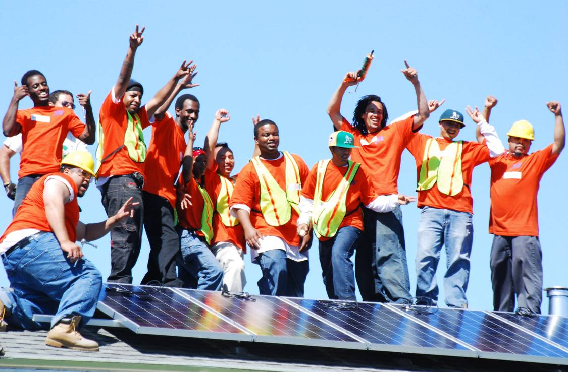 A group of men stand on a rooftop behind a solar panel they just installed. They are wearing orange shirts and construction vests, and raising their arms in a celebratory way.